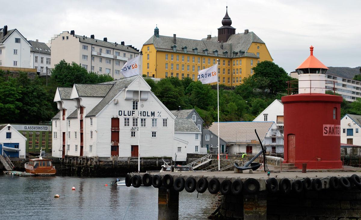 Fiskerimuseet i Ålesund, sett fra Skansekaia. I forgrunnen ser vi selve fyrtårnet «Moljå», ytterst på piren som går ut fra Molovegen. I bakgrunnen ruver ærverdige Aspøy skole.