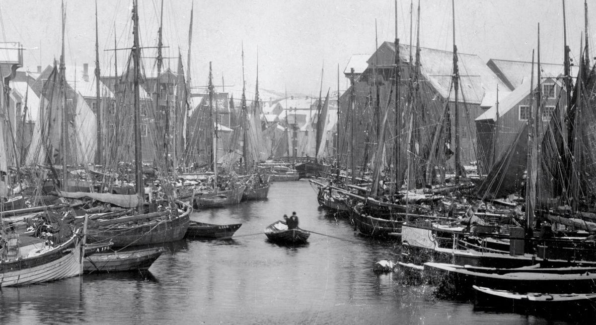 """Landliggedag under torskefisket i 1890-åra. Ålesundet er tettpakka av bankskøyter. Til høyre, fortøyd ved Lorkeneset, ligger brannsprøyta """"Parat"""" som siden skulle gjøre en heroisk, men fånyttes innsats under bybrannen i 1904. (Aalesunds Museums fotosamling)"""