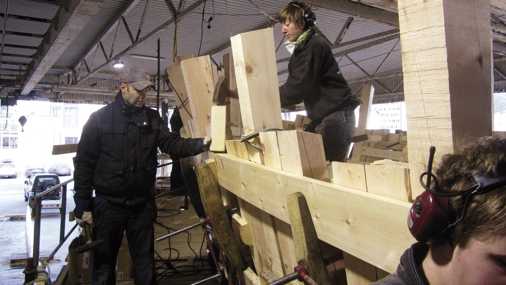 Målargongen må ned et lite hakk, og Lars holder en kloss mot planken slik at Josefine kan gi den en dask med slegga.