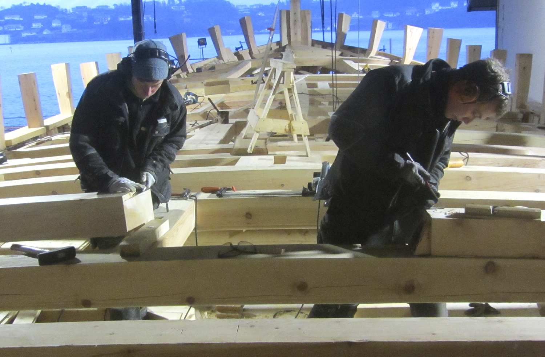 Bildet viser at bjelkelaget snart er ferdig, og at Josefine og Jørgen er konsentrerte om oppgaven. Vi må derfor tenke igjennom materialkvaliteten i dekket som skal ligge ovenpå bjelkelaget.